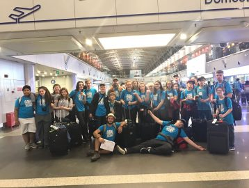 Student group stands together for a photo at Beijing airport