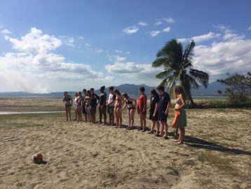 Group of teenagers stand on the beach during an orientation for a trip to Fiji
